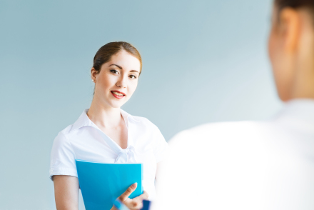 young woman holding blue folder facing a man who is interviewing her for a job