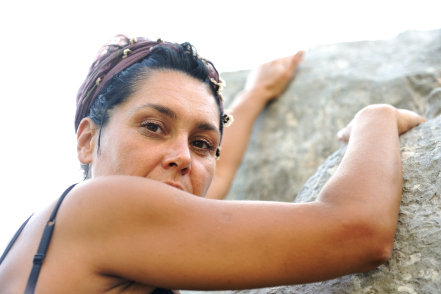 Female climbing rocks on mountain