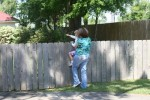 woman holding child up to fence