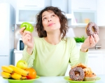 Lady deciding between fruit or donut