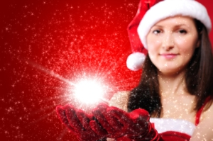 Girl with Santa hat holding hands out with red gloves and a globe of star light in them