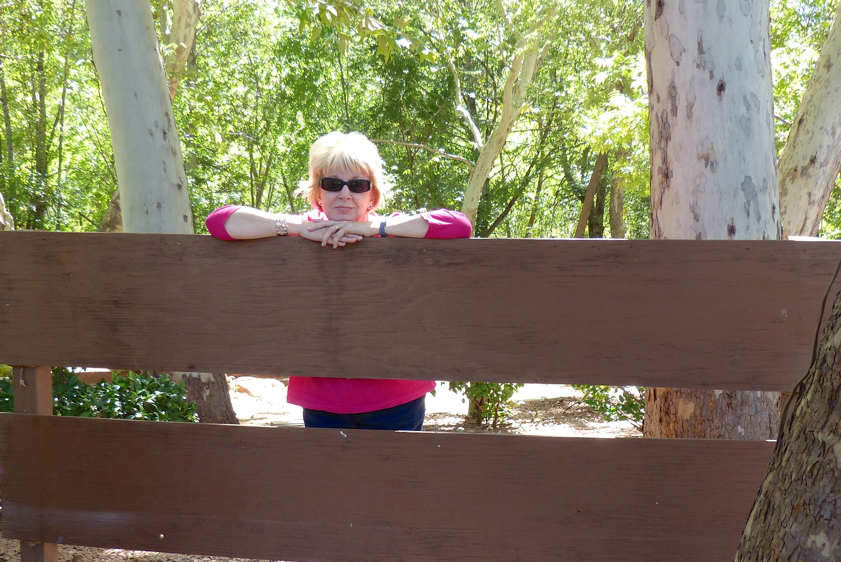 Gail with arms resting on top of fence she is standing behind