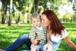Mom holding young son in green grass