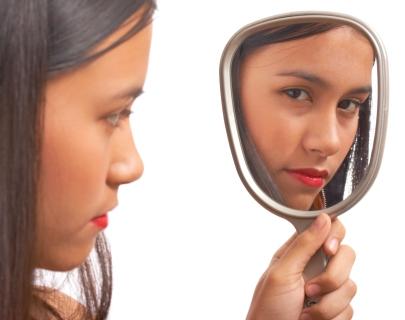 Girl looking at herself in handheld mirror