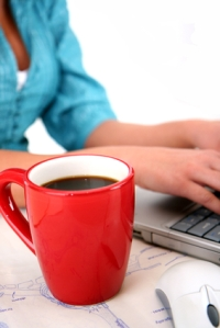 woman typing with coffee