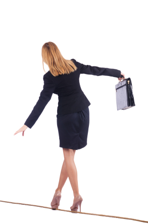 Business woman balancing on tightrope