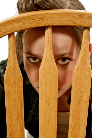 Woman looking thru back of chair