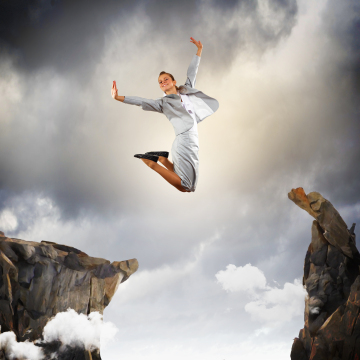 business woman jumping across abyss