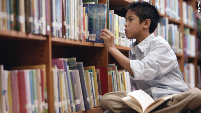 Boy pulling book from library shelf
