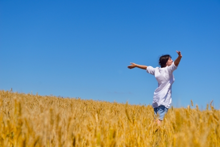 Woman in wheat field arms out-stretched