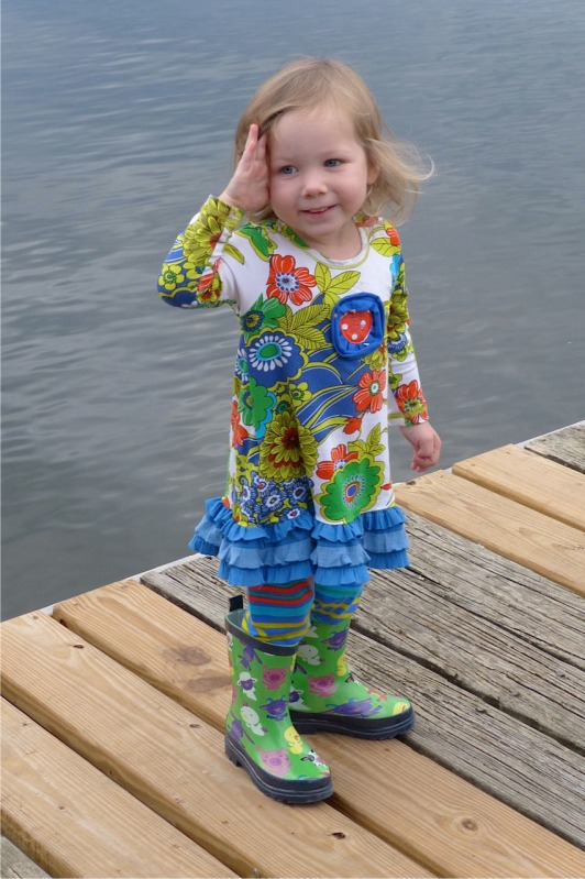 two-year old girl in colorful outfit with green rubber boots standing on pier.