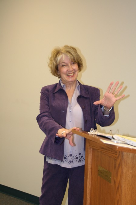 Gail in purple speaking with hand gestures