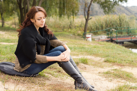 Lonely young woman sitting holding her knees, looking down