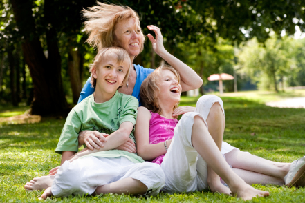Two children laughing with mom on ground