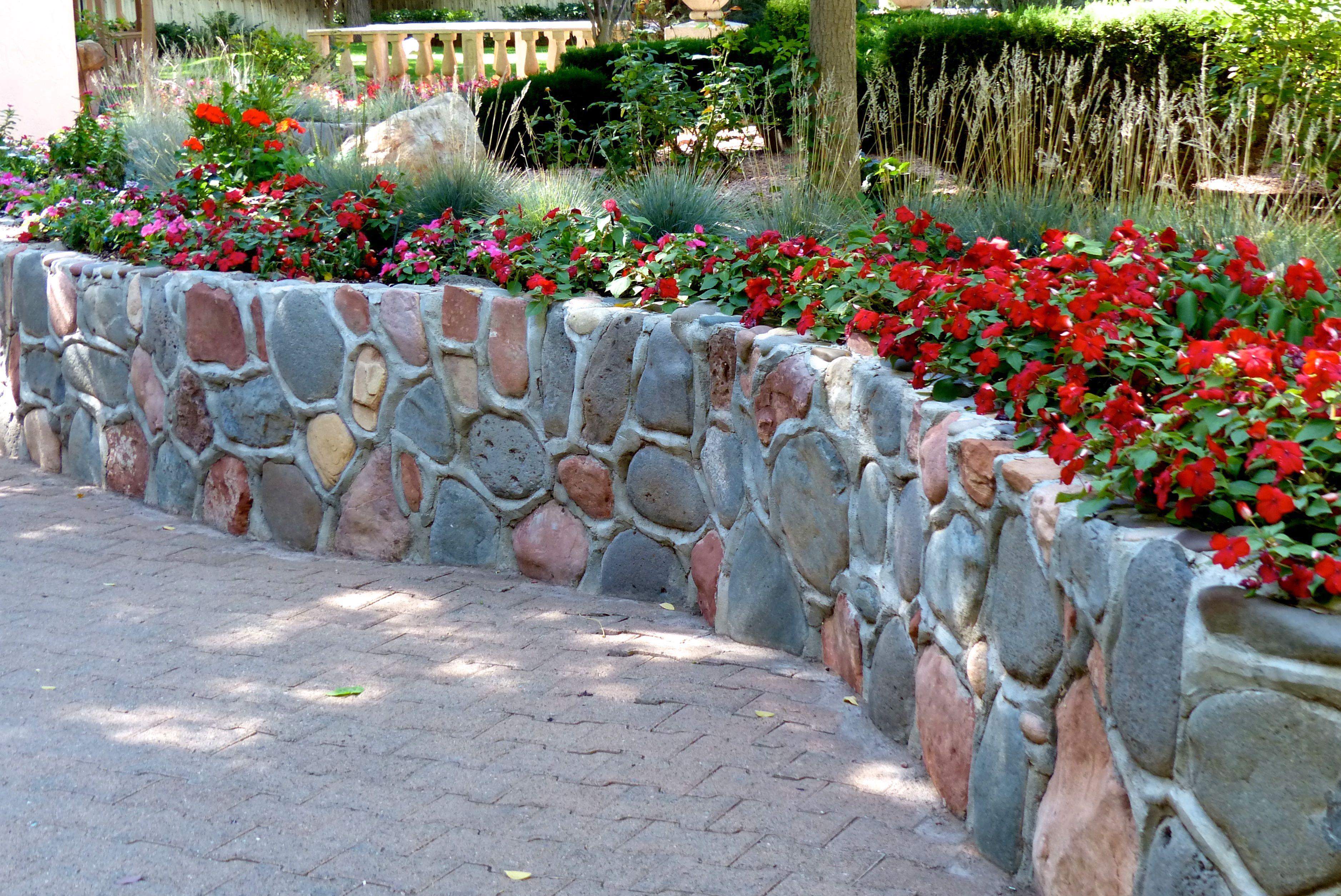 low curved stone wall topped with red flowers
