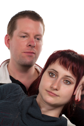 Man looking over woman's shoulder; neither is happy