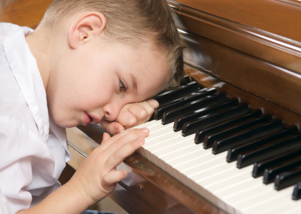 Young Boy with Head on Hand Playing the Piano