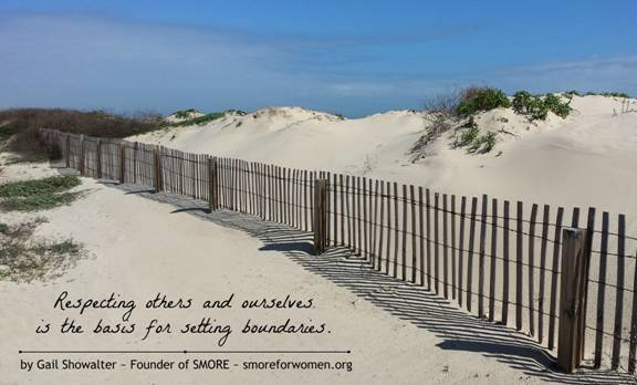 Photo graphic of wooden fence at angle across sand drifts at beach