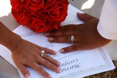 Bride and groom hands on marriage certificate