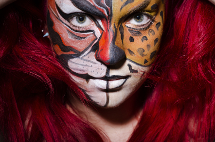 25699851 Woman with face painting in dark room