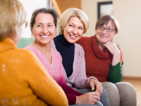 35201552 - portrait of senior women having discussion indoor and laughing. focus on one