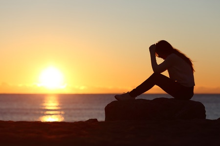 Silhouette of woman with head in hands sitting on rock at shore at sunrise