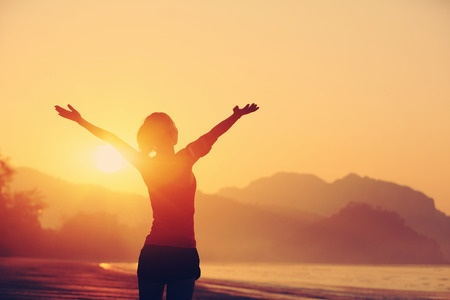Joyful woman with raised arms at sunrise