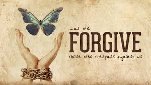 Open hands that are chained at the wrist and releasing a butterfly with quote - As we forgive those who trespass against us