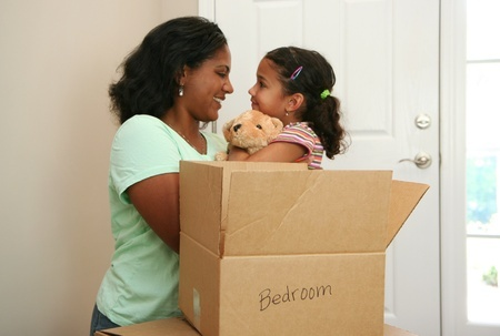 Happy mother and child unpacking in new home