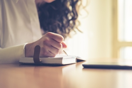25583414 - beautiful woman at home writing and working with diary and smart phone