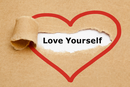 Text Love Yourself behind brown paper torn away