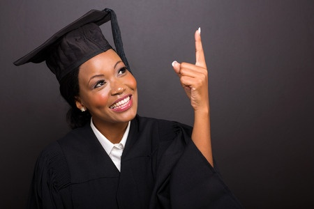 Young lady in cap and gown pointing upward