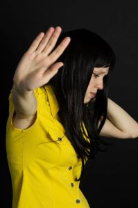 60120986 - violence, suffering girl showing stop hand on a black background