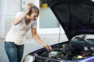47724865 - confused young woman looking at broken down car engine on street