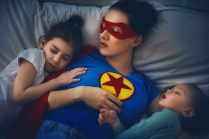 Mom in Super Woman shirt is asleep with a child on each side